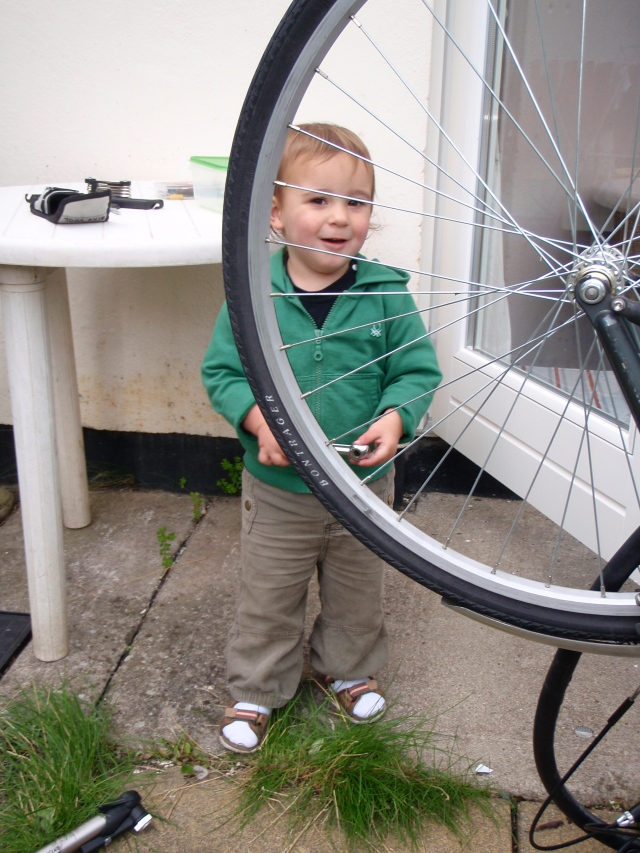 Hugh likes 'bice.' Here he helps Ken mend a flat tyre.